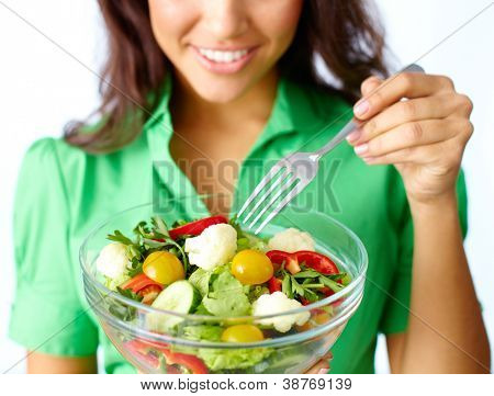 Close-up of fresh vegetable salad being eaten by female