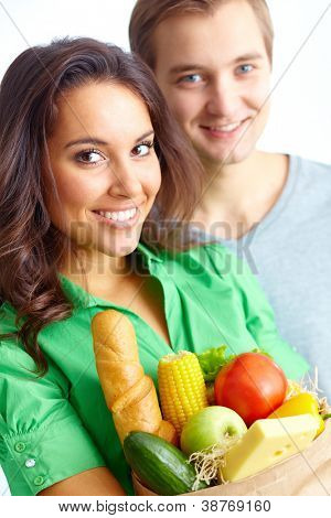 Happy female with healthy food looking at camera with young man on background