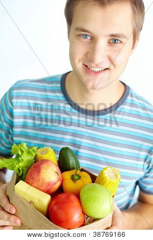 Image of happy young man wit hpack of healthy food looking at camera
