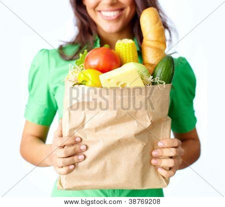 Imagem de saco de papel grande cheio de diferentes frutas e legumes em mãos femininas