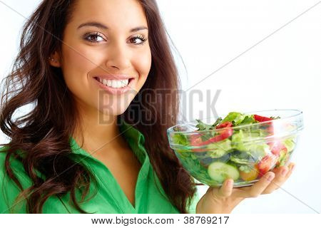 Close-up of pretty girl holding fresh vegetable salad in glass bowl