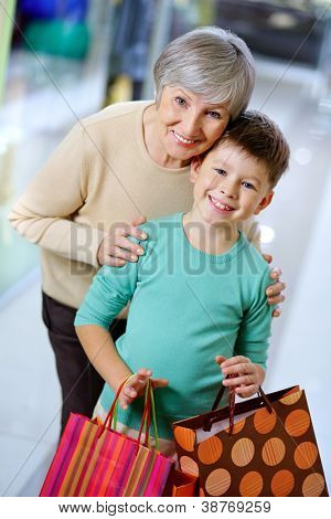 Retrato de uma criança feliz com paperbags e sua avó no shopping