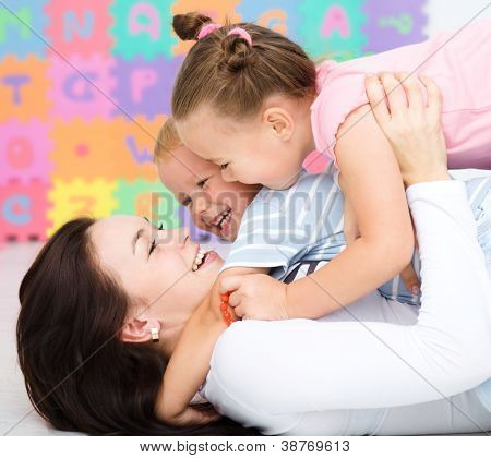 Mother with her children are having fun rolling on a floor