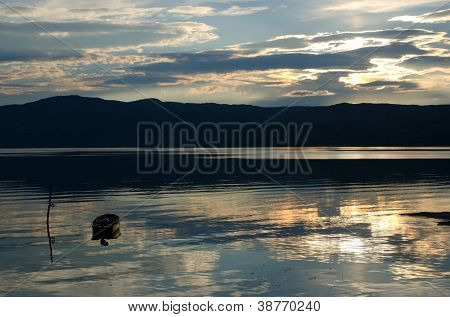 Sunset over fjord with old boat, Finnmark, Norway
