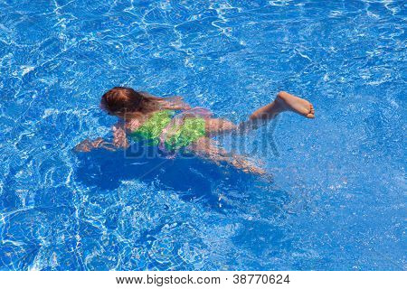 children girl swimming underwater in blue tiles pool