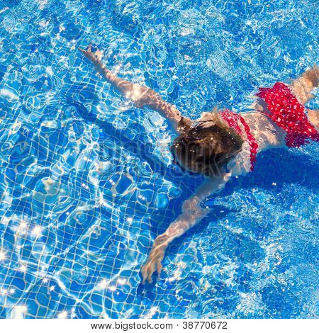 bikini kid girl swimming on blue tiles pool in summer vacation