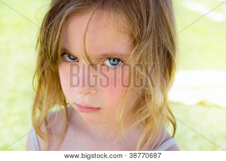 Angry blond children girl portrait looking at camera