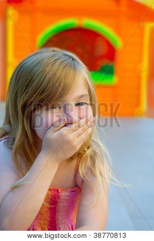 Niño rubio chica gesto divertido mano en la boca en el patio con vestido de verano