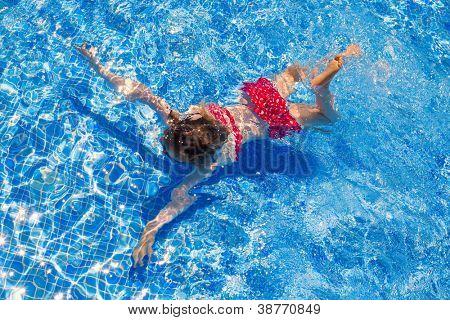 bikini kid girl swimming on blue tiles pool in summer vacation