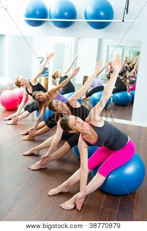 Aerobic Pilates women group with stability ball in a row on mirror gym