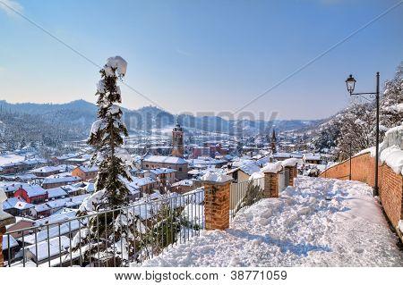 Vista aérea en pequeño pueblo cubierto de nieve entre colinas en Piamonte, norte de Italia.