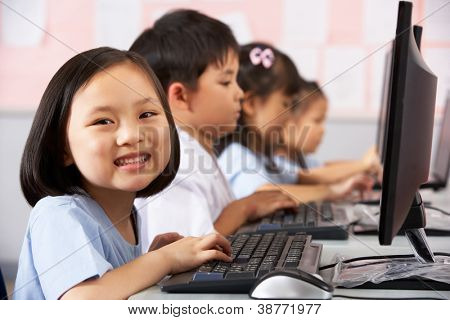 Female Pupil Using Keyboard During Computer Class In Chinese School Classroom