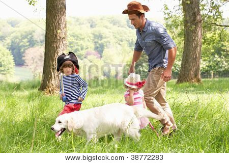 Father Playing Exciting Adventure Game With Children And Dog In Summer Field