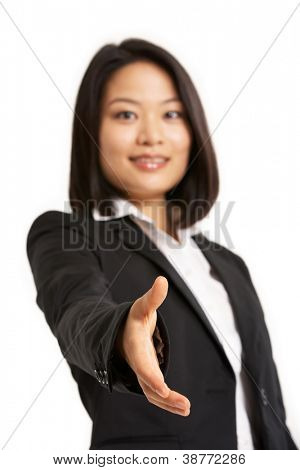 Studio Portrait Of Chinese Businesswoman Reaching Out To Shake Hands