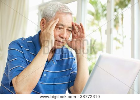 Worried Senior Chinese Man Sitting At Desk Using Laptop At Home