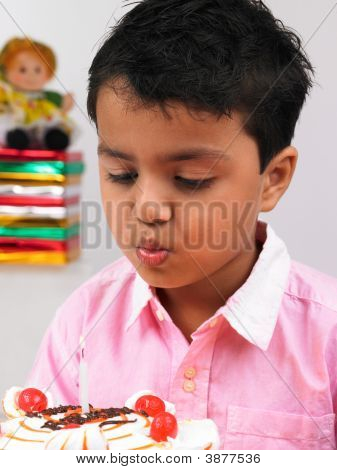 Asian Kid Blowing The Candle On His Birthday