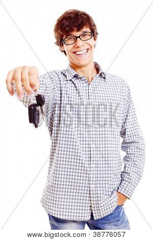 Happy latin teenager in black glasses holding out car keys. Isolated on white background, mask included