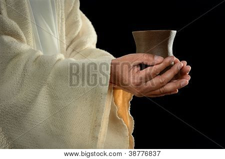 Jesus hands holding cup over dark background