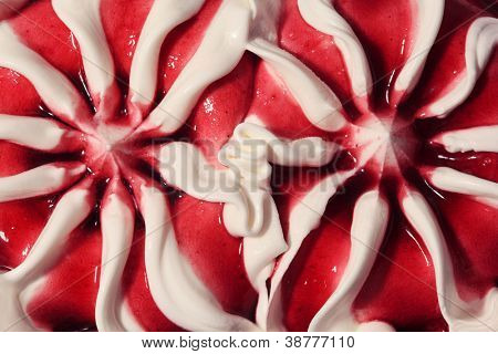 Close up of sweet dessert ice cream - two symmetry flowers from cream and red jelly.