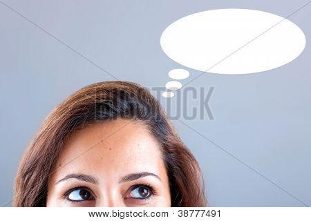 Thinking woman looking up. Including thought bubble with copy space on grey background.