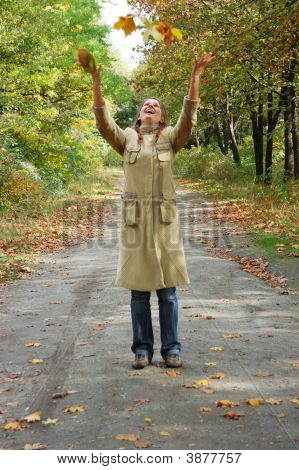 Happy Young Woman Tosses Up Yellow Leaves