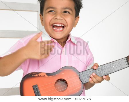 Asian Boy Playing A Toy Guitar