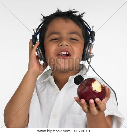 Asian Boy Eating A Red Apple And Listening To Music