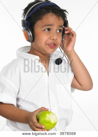 Boy Eating A Green Apple And Listening To Music