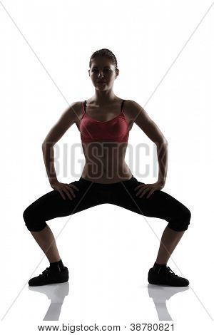 sport young athletic woman doing squatting, silhouette studio shot over white background