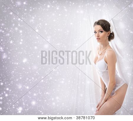 Joven novia sexy en lencería erótica sobre fondo de Navidad