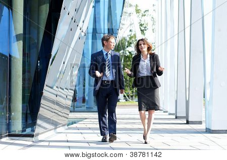 Business people walking and talking in the street