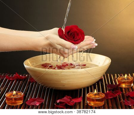 woman hands with wooden bowl of water with petals, on brown background