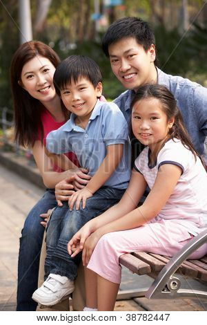 Chinese Family Walking Sitting On Bench In Park Together