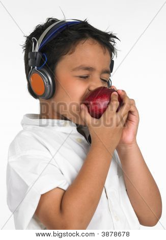 Boy Eating Apple And Listening To Music