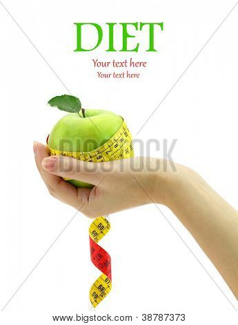 Diet concept. Female hand holding fresh apple with measuring tape