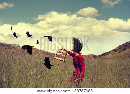 a girl walking in a field with a flock of birds