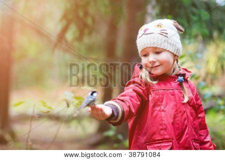 Adorável menina pequena e grande pássaro tit sentado em seu dedo