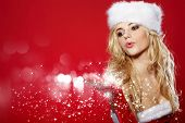 Photo of fashion Christmas girl blowing snow.