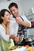 stock photo of 35 to 40 year olds  - Man preparing dinner and making her wife taste the food - JPG