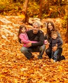 Photo of young happy family in autumnal forest, portrait of friendly family sitting on dry autumn fo