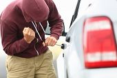View down the side of a car to a man in a hooded top breaking into a car with a screwdriver in order