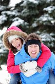 Young excited happy winter couple doing piggyback having fun outside in winter snow forest landscape