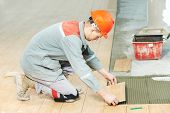 stock photo of overhauling  - Industrial tiler builder worker installing floor tile at repair renovation work - JPG