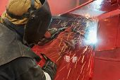 welder worker welding metal by electrode with bright electric arc and sparks during manufacture of m