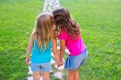 friends sister girls whispering secret in ear in grass garden track park outdoor