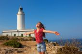 pic of mola  - blue day with kid girl open hands to the wind in la Mola lighthouse of Formentera - JPG