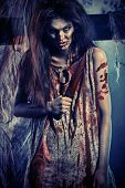 Bloodthirsty zombi with a knife standing at the night cemetery in the mist and moonlight. poster