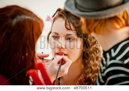 Beautiful young woman having her make up done by a make up artist in a studio