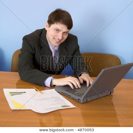 Businessman Sits At Table With The Laptop