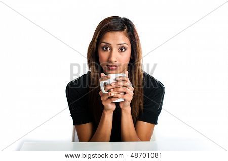 Attractive young asian indian woman enjoying a nice warm drink